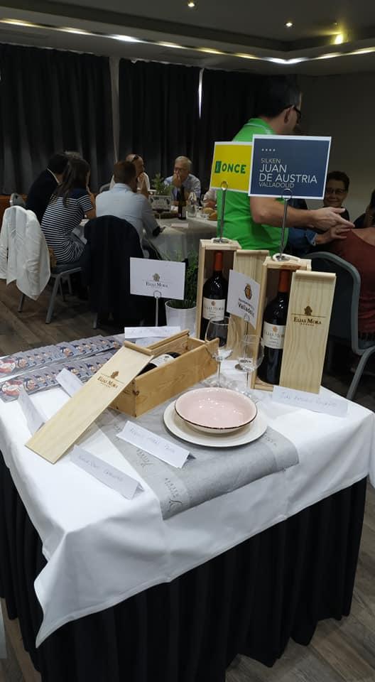 mesa en la que hay carteles de: la once, hotel silken juan de austria, ayuntamiento de valladolid y bodegas elías mora. hay tres cajas de madera con botellas de vino, platos y cds de música